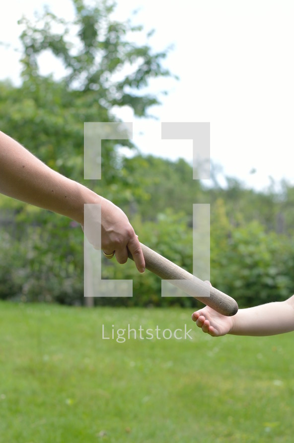 mother giving the relay baton to the next generation into her daughter's hand
