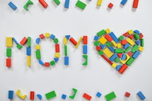 wooden blocks in the shape of a heart and the word mom