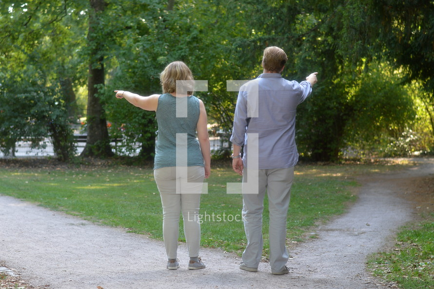 man and woman pointing down different paths