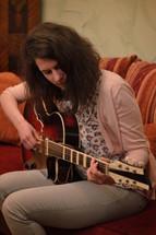 woman praising God and playing guitar