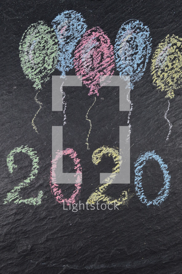 chalk balloons on slate with the number of the year 2020