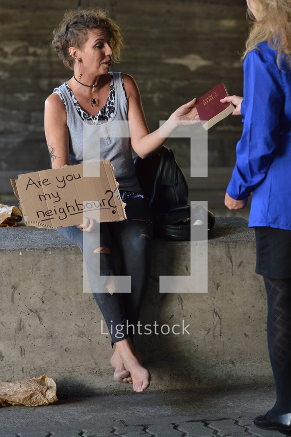 a woman giving a Bible to a woman under a bridge