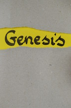 torn open kraft paper over yellow paper with the name of the book GENESIS
