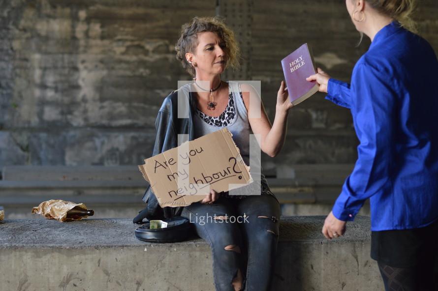 a woman handing a Bible to a homeless woman begging