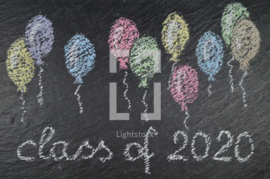 chalk on slate with balloons and the words: class of 2020