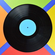 old black vinyl record with blank cyan label centered on multicolored background in a square