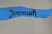 Jeremiah - torn open kraft paper over blue paper with the name of the prophetic book  Jeremiah