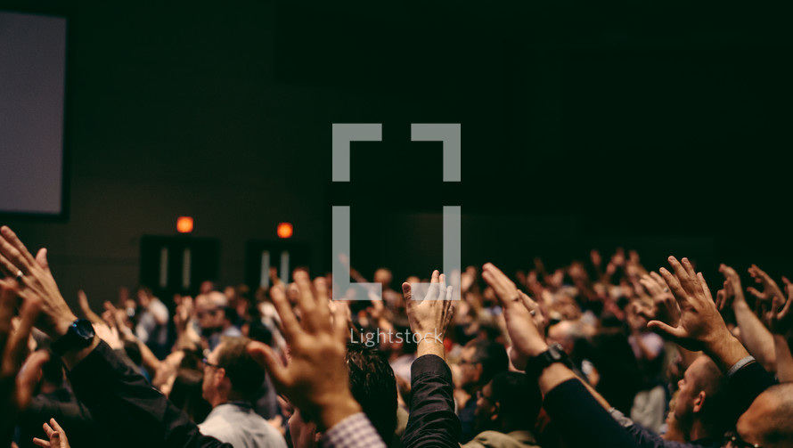 a congregation with raised hands in praise at a worship service