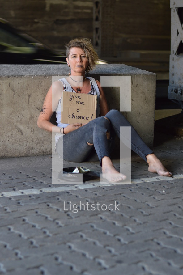 a woman holding a give me a chance sign