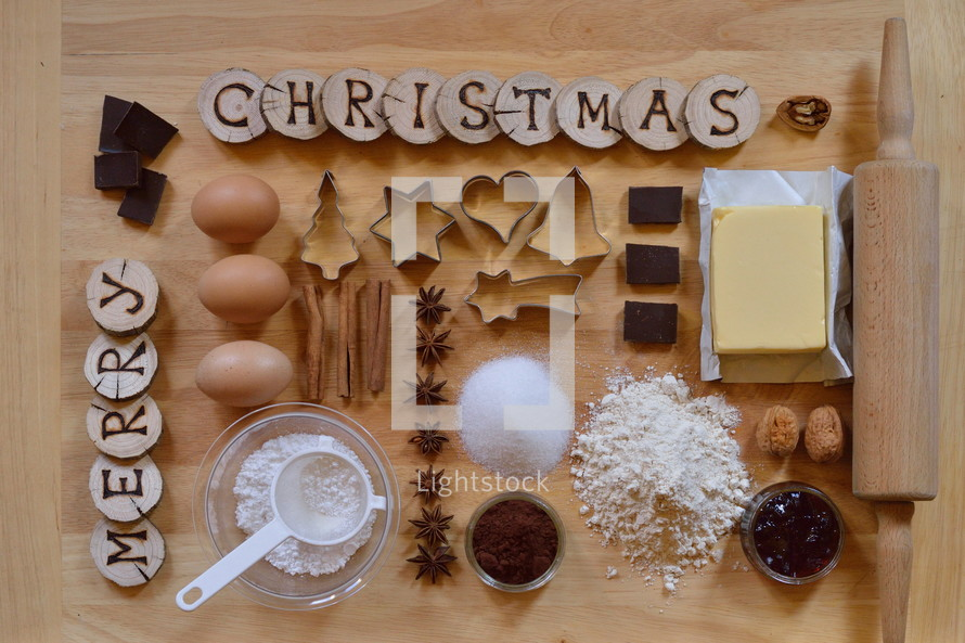 Baking ingredients with wooden pieces and the words MERRY CHRISTMAS burned into them