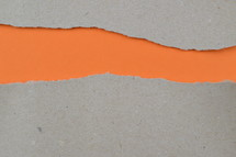 orange under torn gray paper - ripped paper revealing orange blank space for words