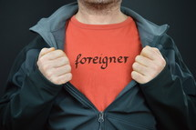 a man exposing the word foreigner written on his red t-shirt under his black jacket