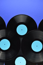 pile of old black vinyl records with blank cyan labels on blue background with copy space above