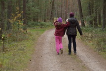 a mother and daughter walking on a dirt road
