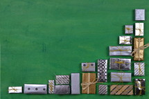 many little silver and golden presents building a border on green wooden background
