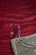 rosary beads and the pages of a Bible