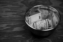 various currency in a bowl on a wood background