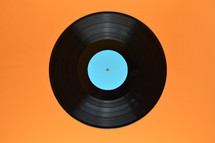 old black vinyl record with blank cyan label central on orange background