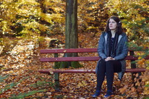 a woman praying on a bench in a park in fall