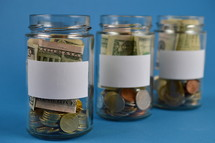 three savings jars full of money with blank labels on cyan background