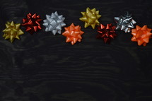 border of holiday bows on black wood background