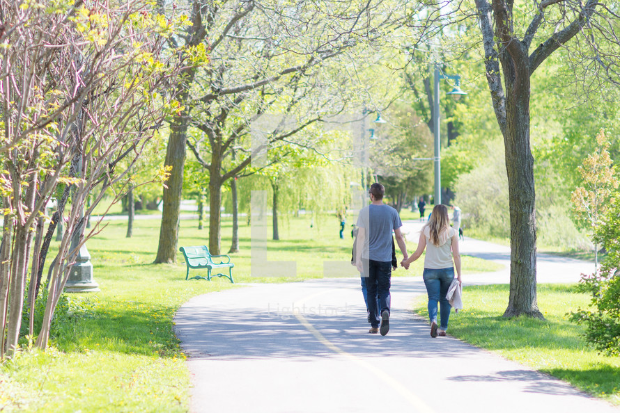 a couple walking holding hands in a park