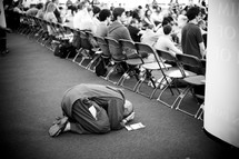 Person kneeling to the ground in prayer during a conference.
