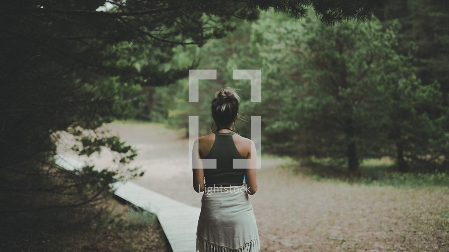 a woman walking outdoors along a wooden path