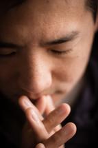 man praying with head bowed