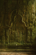 carvings in the walls of a temple in ruins in Cambodia