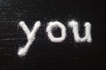 "The word, ""you,"" written in salt on a table."