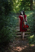 a woman in a red dress with an electric guitar walking through the dark woods
