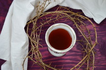crown of thorns, a piece of cloth and a cup of red wine on purple wood