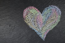 heart shape in sidewalk chalk on slate with copy space to the left