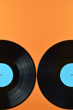 two old black vinyl records with blank cyan labels on orange background