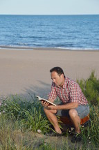 a man reading a Bible sitting on suitcase on a beach