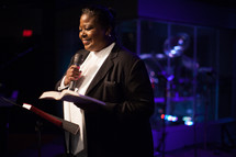 a female pastor leading a worship service