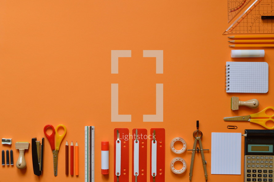 Office or school supply border on orange paperboard