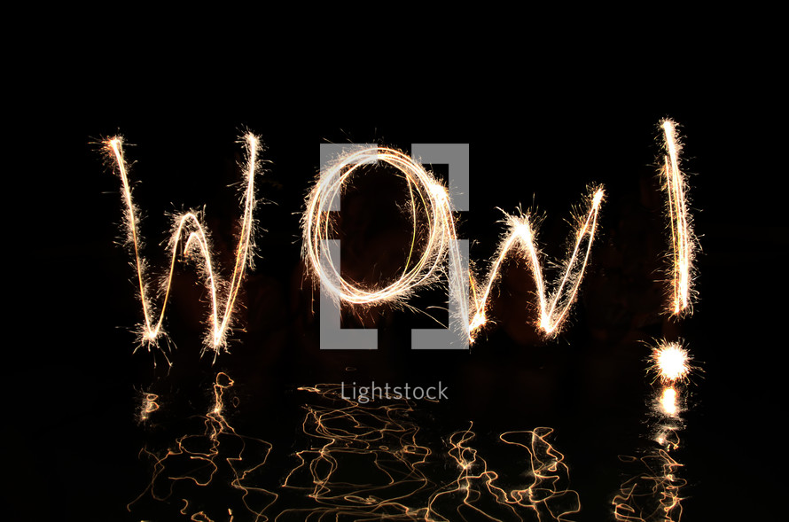 """""""Wow"""" written in fireworks by  four 'artists' standing up the their waists in water."""
