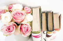 vase of roses and books with book covers