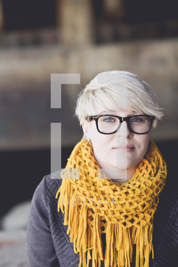 a woman wearing a scarf, reading glasses, and a pixie haircut