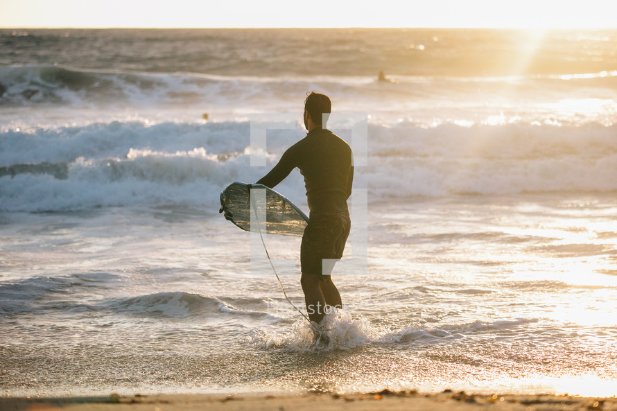 surfer standing in the ocean