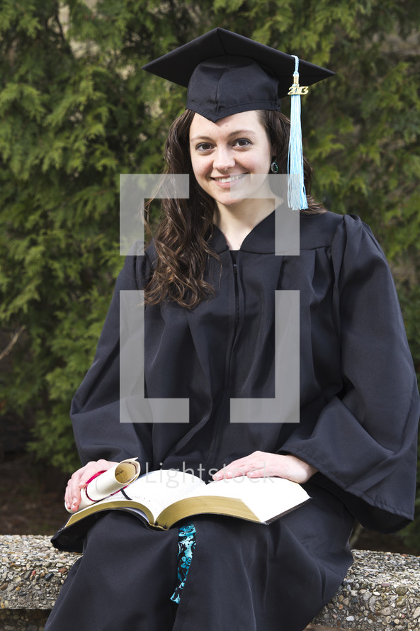 woman sitting outside in her cap and gown at graduation holding a Bible and a diploma