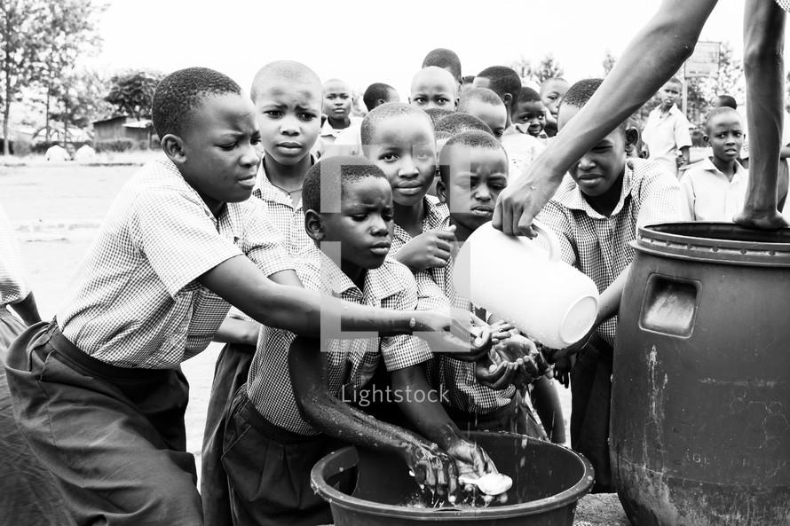 children washing hands in fresh water