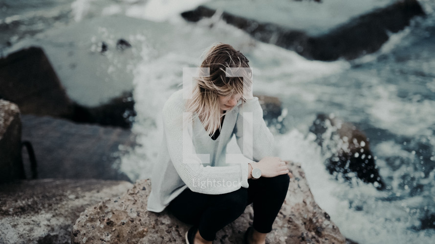 woman sitting on a rock with sea water splashing up