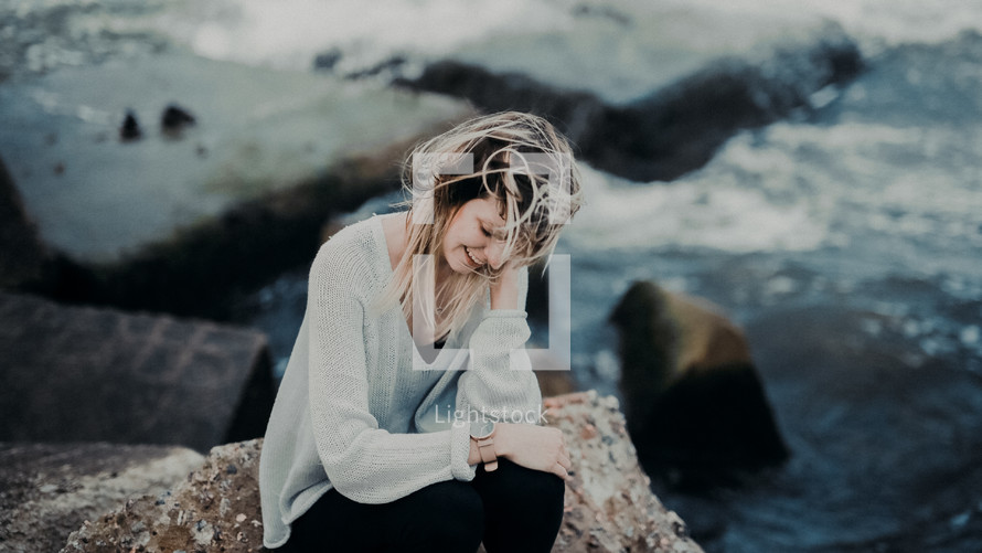 woman sitting on a rock by the sea looking at her watch