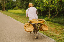 A man riding a bicycle carrying straw baskets