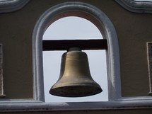A large iron church bell adorning the tower of a local Spanish styled mission that rings to call people to worship.