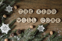 star ornaments, pine cones, snow, pine boughs and the words THE KING WILL COME on wooden slices