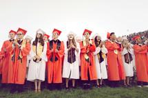 clapping high school graduates